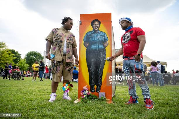 """Guests stand near a painting of Breonna Taylor in her EMT uniform during the """"Praise in the Park"""" event at the Big Four Lawn on June 5, 2021 in..."""