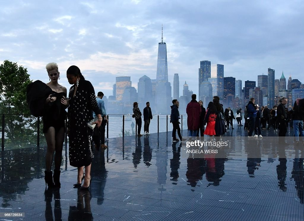Guests stand on the runway in front of the Manhattan skyline before the Saint Laurent Men's Spring/Summer 2019 collection during a runway show in Liberty State Park on June 6, 2018 in Jersey City, New Jersey.