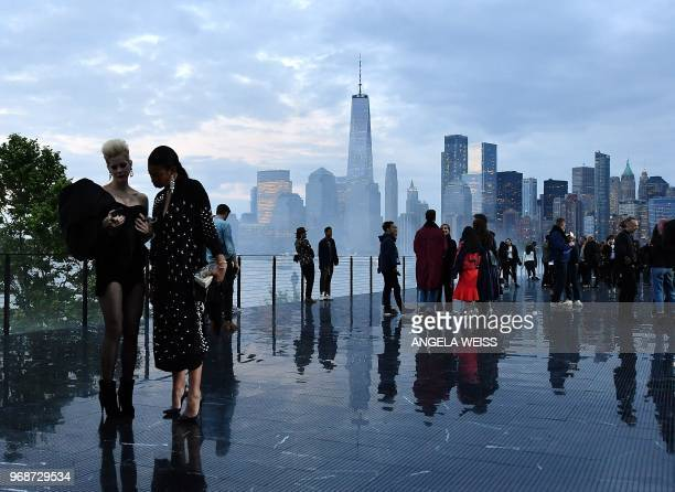 Guests stand on the runway in front of the Manhattan skyline before the Saint Laurent Men's Spring/Summer 2019 collection during a runway show in...