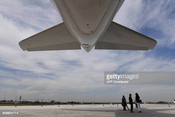 Guests stand under the first Airbus A330 plane to be delivered after the inauguration ceremony of the Airbus Long Range Cabin Completion Centre in...