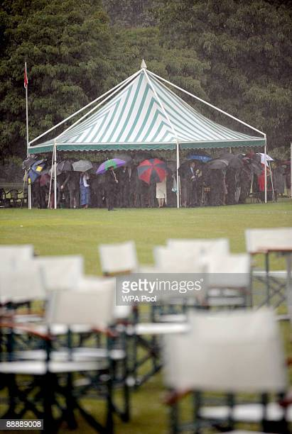 Guests take cover as heavy rain falls the first Royal Garden Party of the summer at Buckingham Palace on July 7 2009 in London England