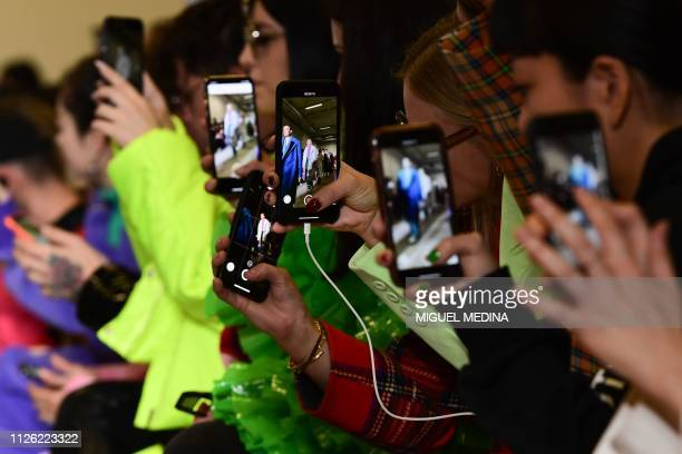 Guests take photos and videos woth their mobile phone during the presentation of the Annakiki women's Fall/Winter 2019/2020 fashion collection on...