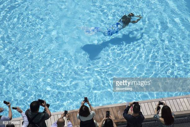 Guests take photos of Mermaid Kat as she performs in the pool aboard the Genting Hong Kong Ltd Genting Dream cruise ship berthed at the Marina Bay...
