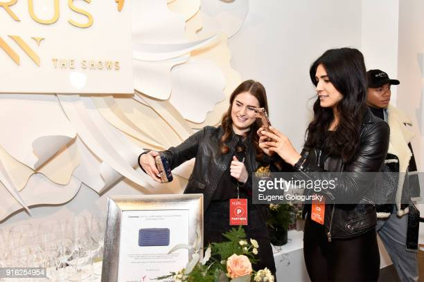 Guests take photos of the Judith Leiber Couture Airstream hand bag in Plum during Papyrus and Judith Leiber host Breakfast Mimosas at IMG NYFW The...