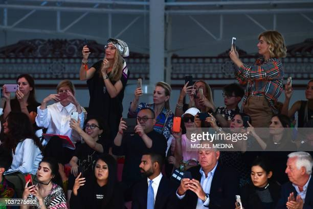 Guests take photos with their mobile phone during the presentation of the Etro fashion house as part of the Women's Spring/Summer 2019 fashion shows...