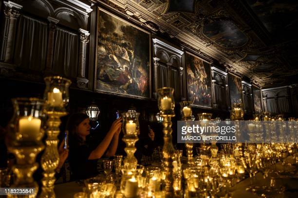 Guests take pictures of the paintings by Italian artist Tintoretto at Scuola Grande di San Rocco in Venice Northern Italy on November 12 within the...