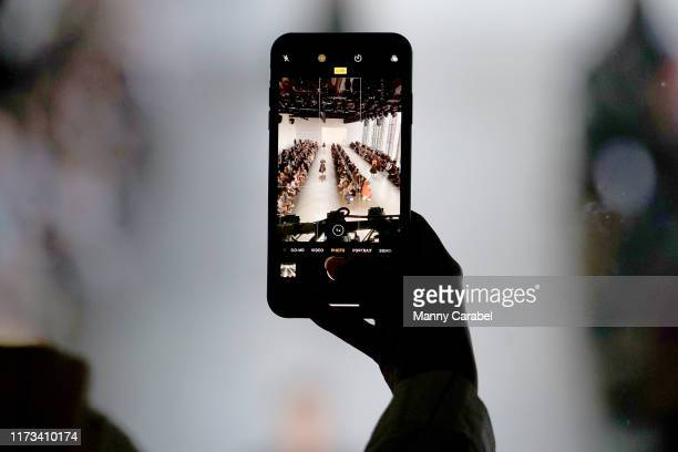 Guests take pictures on their mobile phones of models walking the runway in Gallery II from the Skybox Lounge at Spring Studios during New York...