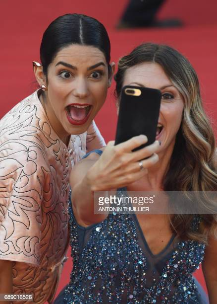 Guests take selfie pictures as they arrive on May 27 2017 for the screening of the film 'Based on a True Story' at the 70th edition of the Cannes...