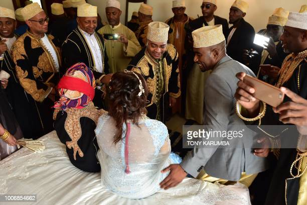 Guests take turns to be photographed with the newly weds during a traditional wedding ceremony at the home of the bride in Moroni July 28 capital of...