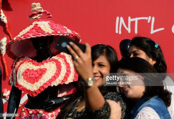 Guests takes a selfie with a mannequin wearing a dress made of condoms during an event to mark International Condom Day in New Delhi on February 13...