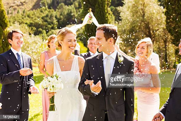 guests throwing confetti on couple during garden wedding - wedding ceremony stock photos and pictures