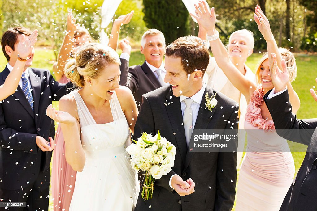 Guests Throwing Confetti On Couple During Reception In Garden : Stock Photo