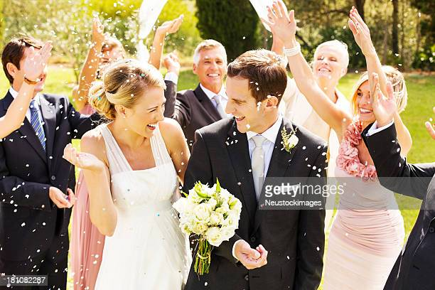 guests throwing confetti on couple during reception in garden - wedding ceremony stock photos and pictures