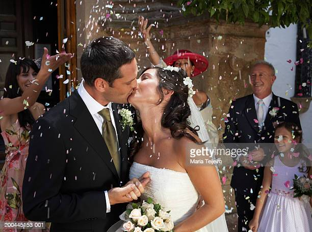 guests throwing confetti over kissing bride and groom, outdoors - church wedding decorations stock pictures, royalty-free photos & images