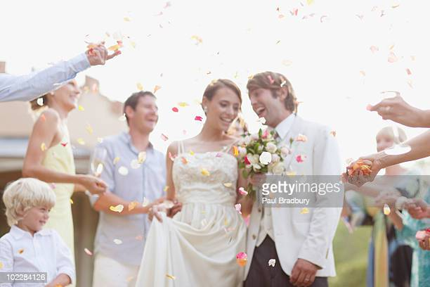 guests throwing rose petals on bride and groom - wedding ceremony stock photos and pictures