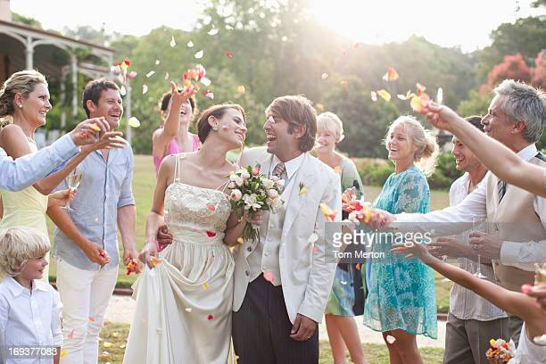 guests throwing rose petals on bride and groom - wedding stock pictures, royalty-free photos & images