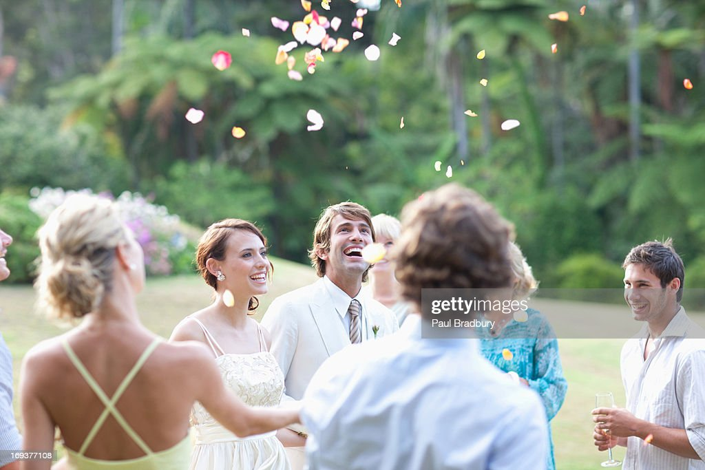 Guests throwing rose petals on bride and groom : Stock Photo
