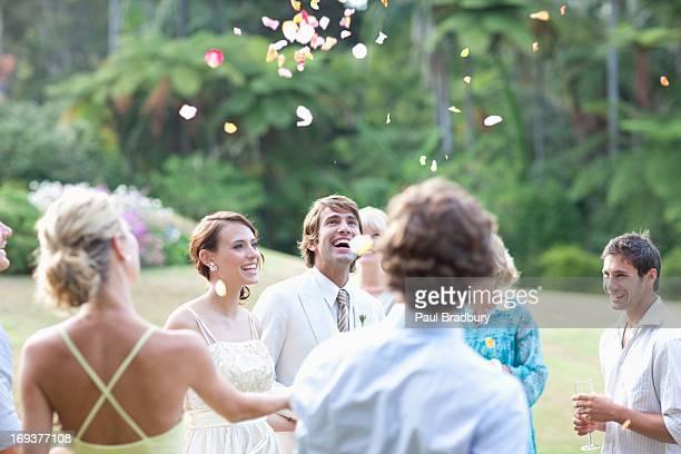 お客様には、バラの花びらを投げるの新郎新婦 - 結婚式 ストックフォトと画像