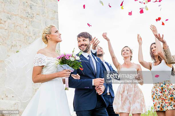 Guests throwing rose petals on bride and groom