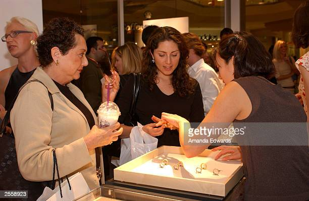Guests try on jewelry at the Knockout Preview Party hosted by Jackie Kallen and Neissing Jewelry in the new Neissing shop at the Beverly Center...
