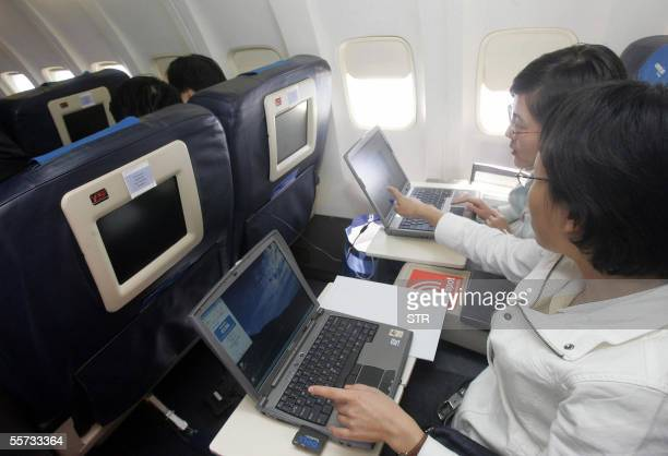 Guests try out the wireless connection to the Internet on their laptops onboard US aerospace giant Boeing's latest aircraft Connexion which allows...