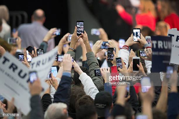 Guests try to get a picture of Republican presidential candidate Donald Trump as he arrives at a rally at Macomb Community College on March 4 2016 in...