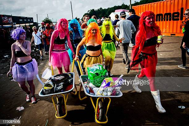 Guests use wheelbarrows to carry their belongings at the Roskilde Festival on July 1 2013 in Roskilde Denmark The Roskilde Festival is one of the...