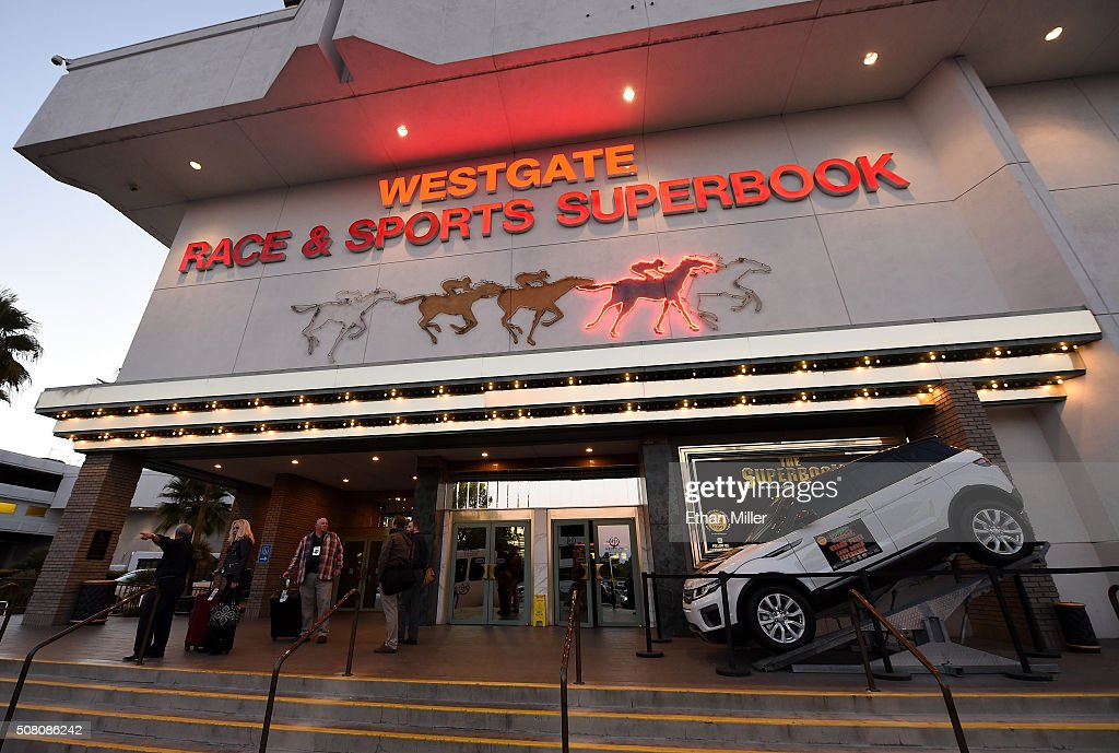 Guests walk by an entrance to the Race & Sports SuperBook at the Westgate Las Vegas Resort & Casino on February 2, 2016 in Las Vegas, Nevada. The newly renovated sports book, currently offering nearly 400 proposition bets for Super Bowl 50 between the Carolina Panthers and the Denver Broncos, has the world's largest indoor LED video wall with 4,488 square feet of HD video screens measuring 240 feet wide and 20 feet tall.