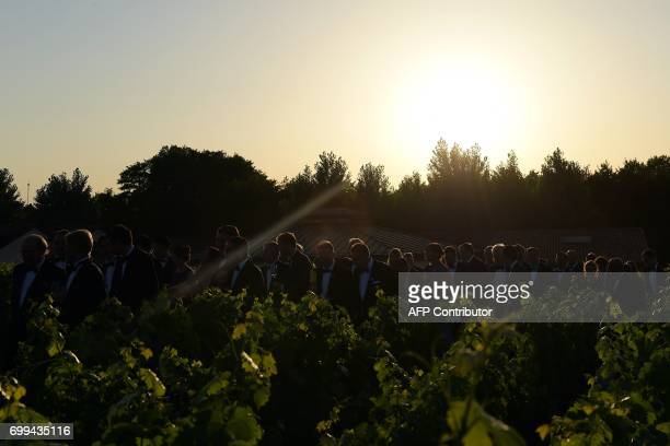 CORRECTION Guests walk in the vineyards during the 65th Fete de la Fleur at Chateau MalarticLagraviere in Leognan southwestern France on June 21...