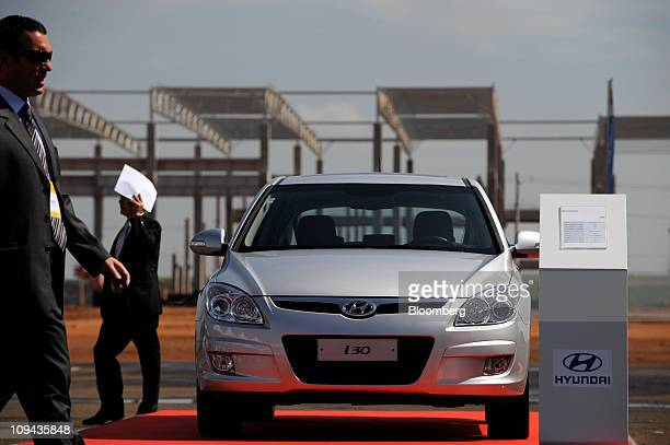 Guests walk past a Hyundai Motor Co I30 sedan during a groundbreaking ceremony for a Hyundai factory in Piracicaba Brazil on Friday Feb 25 2011...