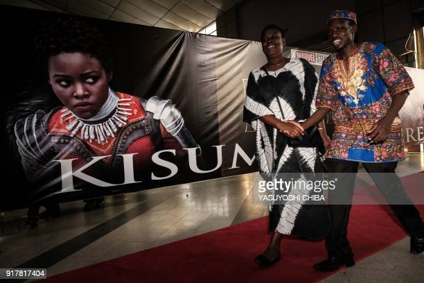 Guests walk past an image of Kenyan actress Lupita Nyong'o before the African premier of the Marvel film 'Black Panther' in Kisumu Kenya on February...