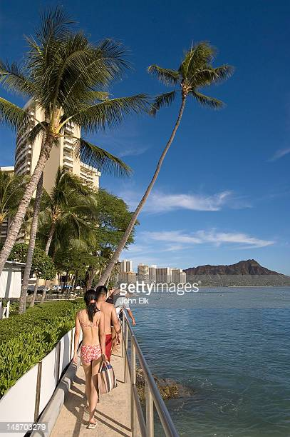 guests walking along waikiki beach, diamond head in background. - ダイヤモンドヘッド ストックフォトと画像