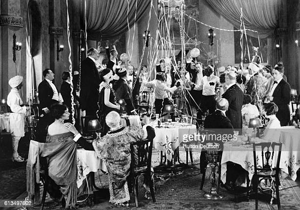 Guests watch a pair of fencers play a round of their sport on the dance floor of a formal party or more likely a masquerade party during the 1920s