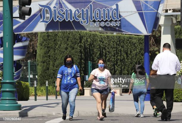 Guests wear face masks as they depart the Downtown Disney District on the first day it reopened following temporary closure due to the COVID-19...
