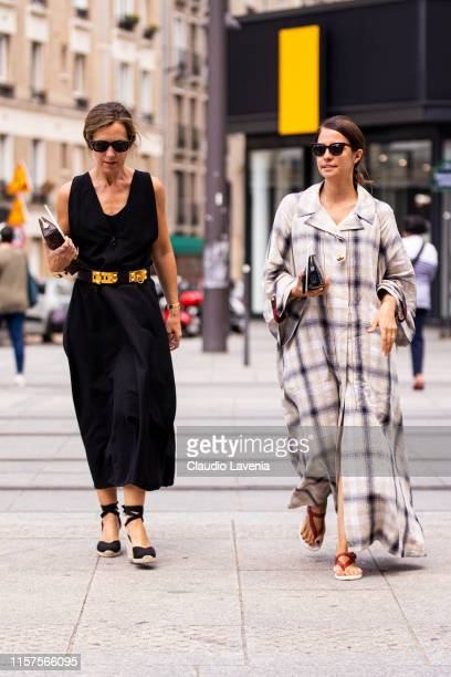 Guests wearing a black dress gold belt and black espadrilles and long checked dress and red sandals are seen outside Jil Sander fashion show on Day 4...