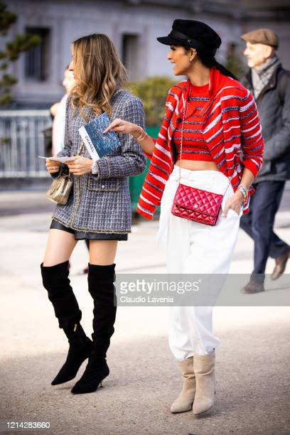 Guests, wearing a blue jacket, black over the knees boots and gold bag , and red striped sweater with matching cardigan, white pants, beige boots and...