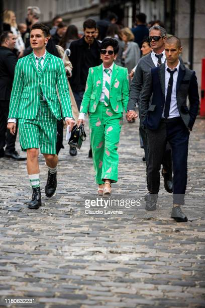 Guests, wearing a green striped blazer with matching shorts and black shoes , and green duck printed suit and black bag , are seen outside the Thom...