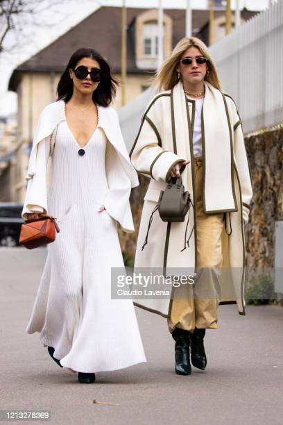 Guests, wearing a white long knitted dress and orange Loewe bag , and white t-shirt, beige pants, cream and green coat and green Loewe bag , are seen...