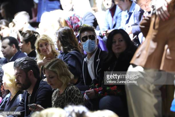 Guests wearing antivirus mask are seen during the Dolce e Gabbana fashion show as part of Milan Fashion Week Fall/Winter 20202021 on February 23 2020...