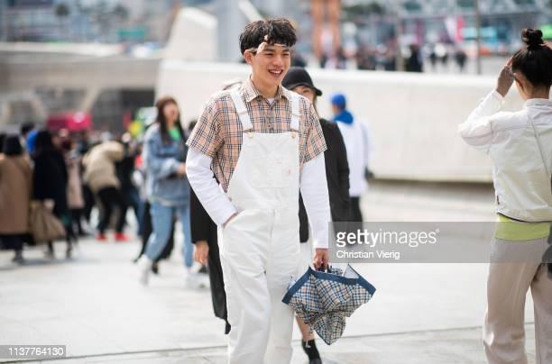 Guests wearing Burberry button shirt bandana white overall seen at the Hera Seoul Fashion Week 2019 F/W at Dongdaemun Design Plaza at Dongdaemun...