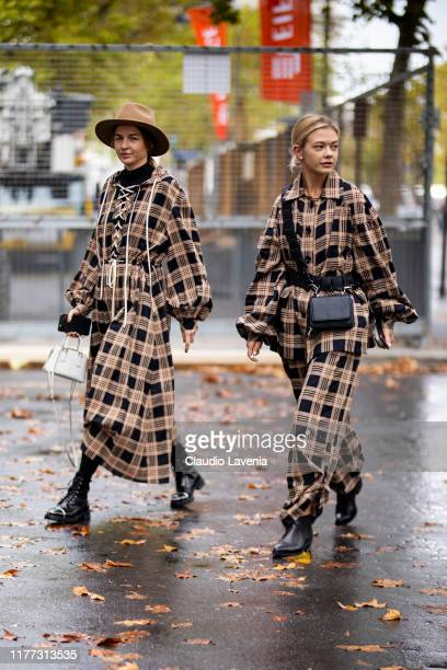 Guests, wearing checked dress, black boots and beige hat , and checked jacket with matching pants, black boots and black bag , are seen outside the...
