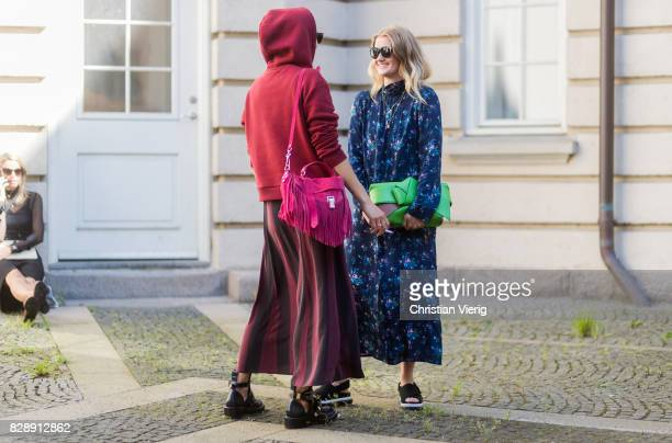 Guests wearing hoody dress with floral print striped skirt outside Holzweiler on August 09 2017 in Copenhagen Denmark