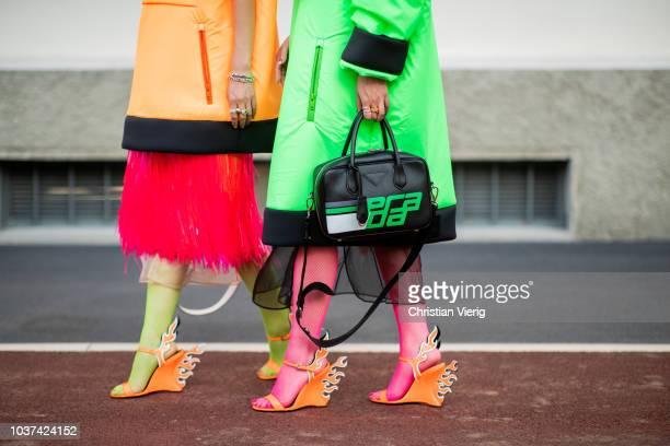 Guests wearing orange and green Prada jacket seen outside Prada during Milan Fashion Week Spring/Summer 2019 on September 20 2018 in Milan Italy