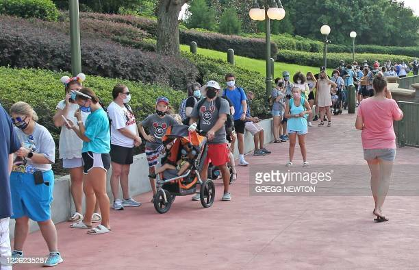 Guests wearing protective masks wait to pick up their tickets at the Magic Kingdom theme park at Walt Disney World on the first day of reopening, in...