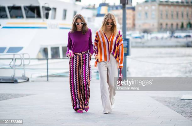 Guests wearing purple knit multi colored wide leg pants pink clutch and a guest wearing striped button shirt wide leg pants red Chanel bag seen...