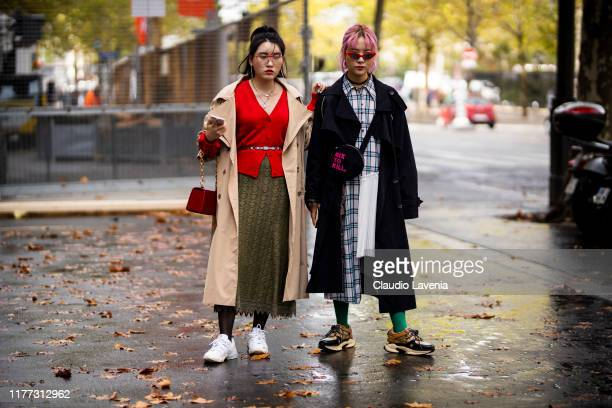 Guests wearing red sweater green lace skirt white sneakers beige trench coat and red bag and checked shirt dress black trench coat brown sneakers and...