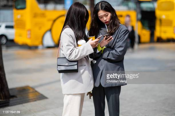 Guests wearing suits looking at their phone seen at the Hera Seoul Fashion Week 2019 F/W at Dongdaemun Design Plaza at Dongdaemun Design Plaza on...