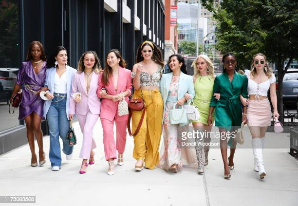 Guests wearing vibrant outfits walk together during New York Fashion Week at Spring Studios on September 07, 2019 in New York City.