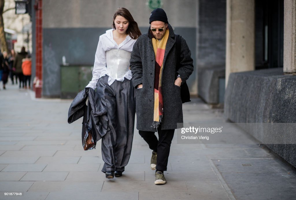 Guests wearing wool coat, beanie, corset, silver suit during London Fashion Week Men's January 2018 on January 6, 2018 in London, England.