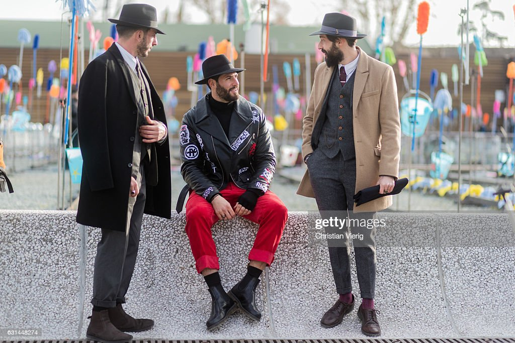 Guests wearing wool coat, hat, sunglasses, red pants, suit, boots, leather shoes on January 10, 2017 in Florence, Italy.